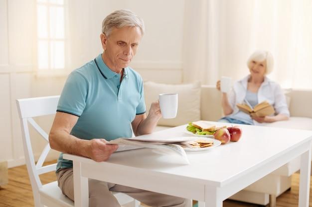 Homem idoso inteligente e focado lendo um jornal enquanto segura uma xícara de café e toma seu café da manhã saudável com sua esposa