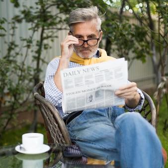 Homem idoso lendo jornal de tiro médio