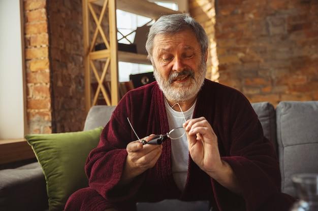 Homem idoso mais velho maduro durante a quarentena, percebendo a importância de ficar em casa durante o surto de vírus