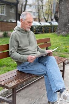 Homem idoso moderno lendo jornal