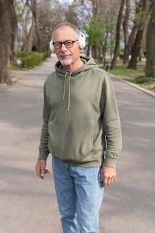 Homem idoso moderno ouvindo música em um fone de ouvido