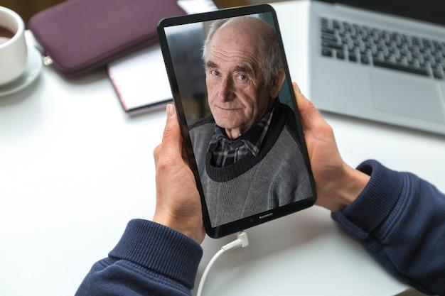 Homem idoso na tela do tablet. chamada de vídeo online.