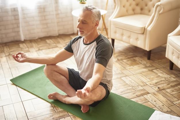 Homem idoso no abrandamento da meditação da posição de lótus.