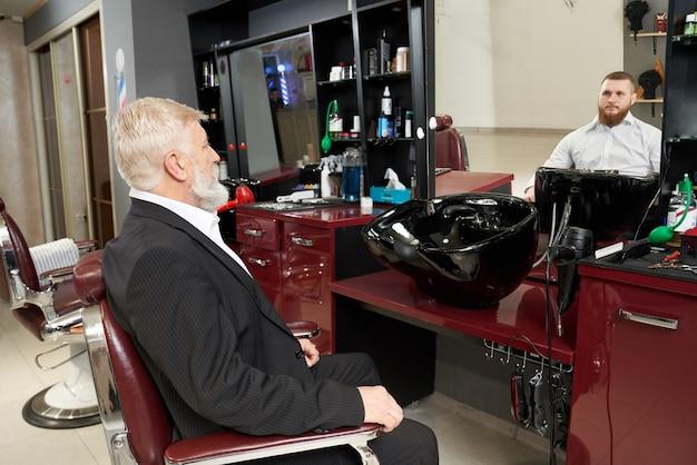 Homem idoso olhando reflexo no espelho de barbearia.