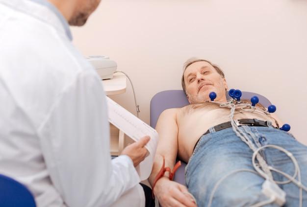Homem idoso otimista e amigável deitado em uma cama com sensores acoplados ao peito enquanto seu cardiologista lê seu eletrocardiograma