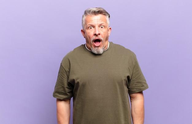 Homem idoso parecendo muito chocado ou surpreso, olhando com a boca aberta dizendo uau