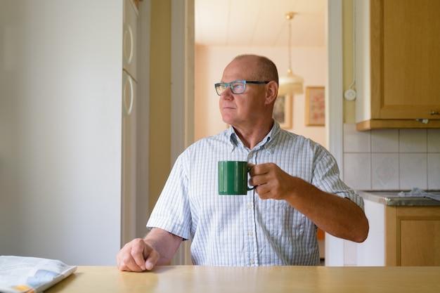 Homem idoso pensando e bebendo café perto da janela