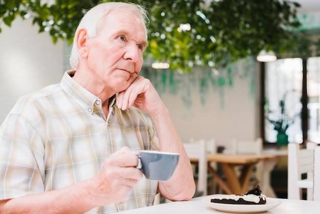 Homem idoso pensativo, bebendo chá