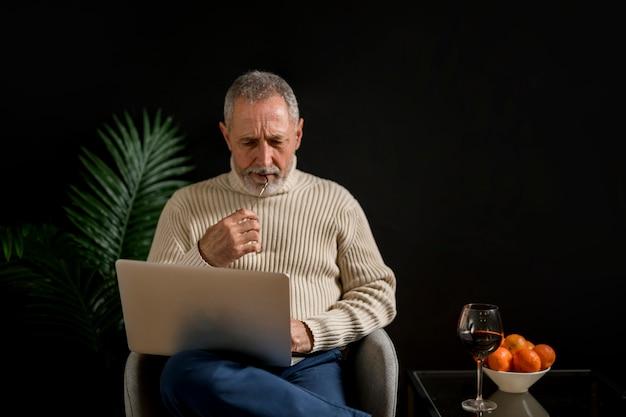 Homem idoso pensativo com laptop