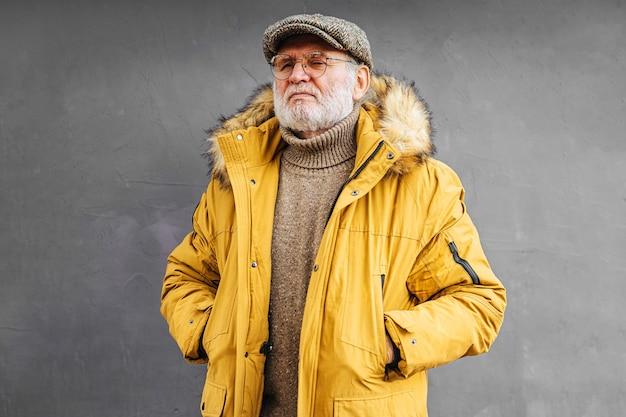 Homem idoso pensativo em agasalhos elegantes de mãos nos bolsos
