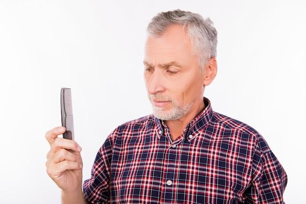 Homem idoso perturbado segurando um pente isolado