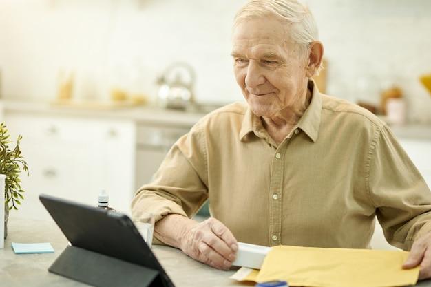 Homem idoso positivo usando tablet para entrar em contato com seu médico