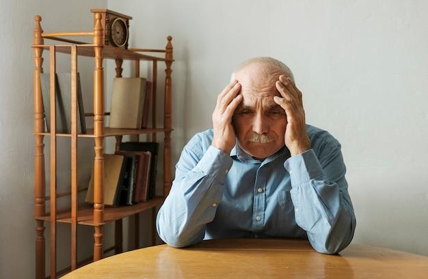 Homem idoso preocupado com a cabeça nas mãos
