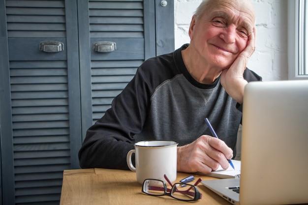 Homem idoso que trabalha no portátil, sorrindo, olhando a tela, bebendo o café.