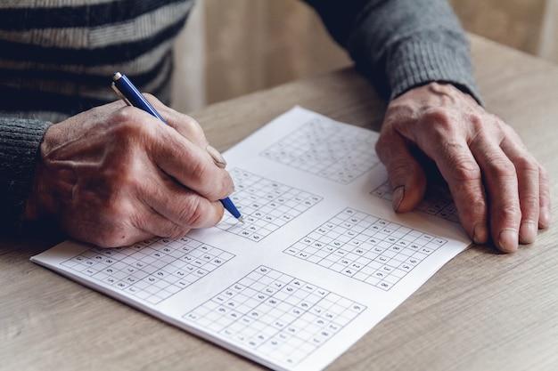 Homem idoso resolve sudoku ou palavras cruzadas