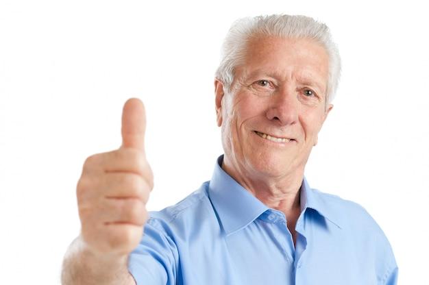 Homem idoso satisfeito e feliz, mostrando o polegar isolado no branco