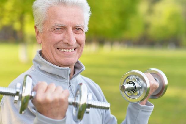 Homem idoso se exercitando com halteres no parque