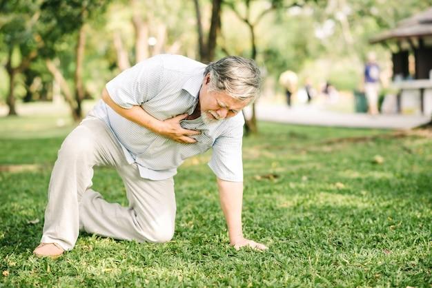 Homem idoso segurando o peito e sentindo dor, sofrendo de ataque cardíaco ao ar livre no parque