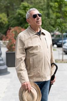 Homem idoso segurando um chapéu de tiro médio