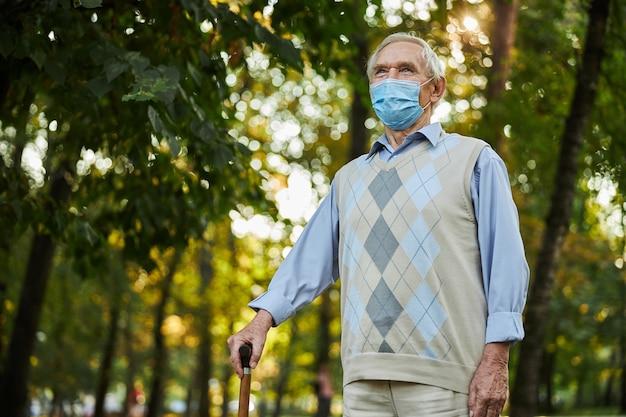 Homem idoso segurando uma bengala na mão enquanto olha para longe no parque