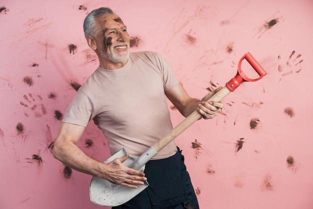 Homem idoso segurando uma pá como se estivesse segurando uma guitarra