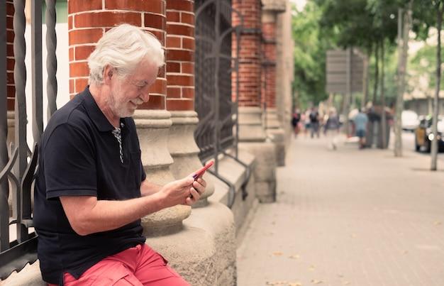 Homem idoso sentado ao ar livre em uma rua da cidade usando um telefone celular, idoso aposentado sorrindo