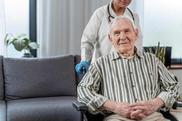 Homem idoso sentado em uma cadeira de rodas ao lado de um médico