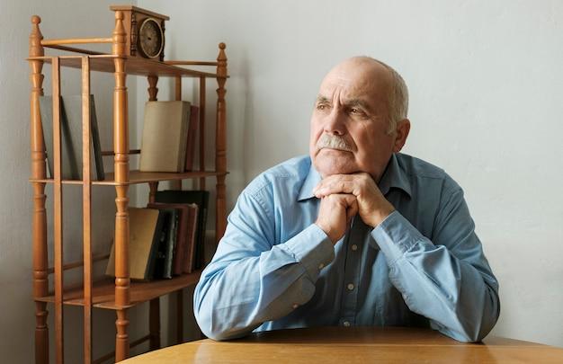 Homem idoso sentado em uma mesa pensando