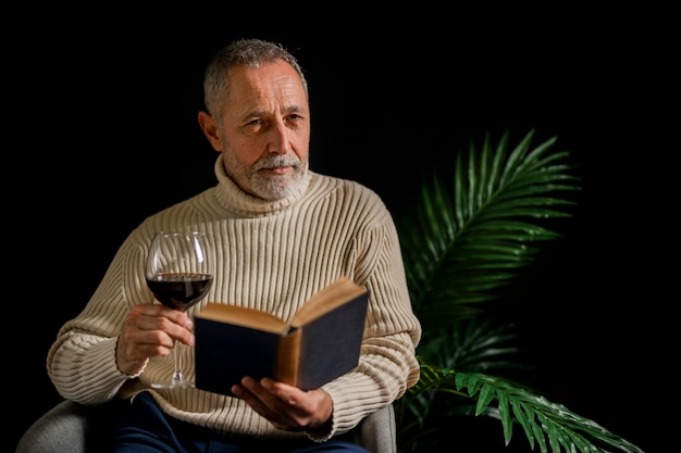 Homem idoso sério com livro e vinho