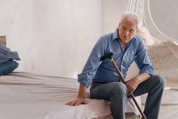 Homem idoso sério de cabelos grisalhos sentado sozinho na sala segurando uma bengala enquanto olha para você