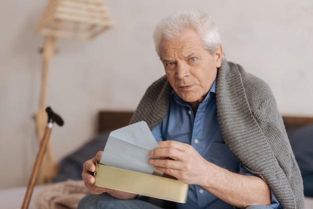 Homem idoso sério e pensativo sentado na cama e pegando uma carta enquanto segura a caixa de correio
