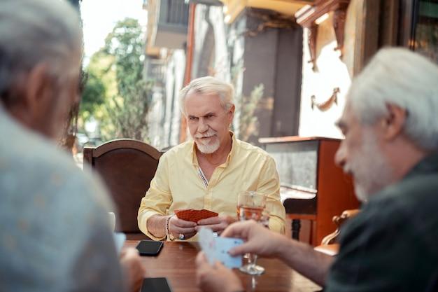 Homem idoso sério. homem idoso barbudo sério jogando com amigos à noite