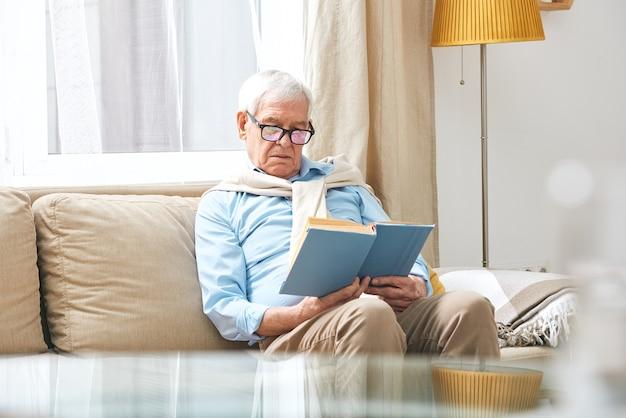 Homem idoso sério usando óculos, sentado no sofá e lendo um livro interessante na sala de estar