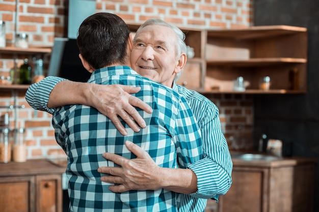 Homem idoso simpático e alegre sorrindo e abraçando seu pecado enquanto expressa seus sentimentos por ele