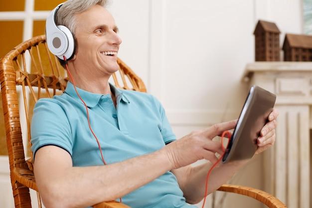 Homem idoso simpático e positivo sentado em uma cadeira pesquisando algumas músicas on-line usando fones de ouvido