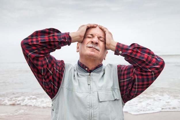 Homem idoso sofrendo de dor de cabeça no fundo do mar