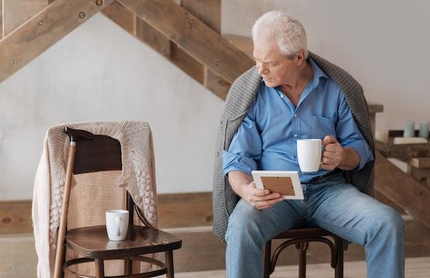 Homem idoso sombrio olhando para a cadeira vazia perto dele e se lembrando de sua esposa enquanto segura a foto dela