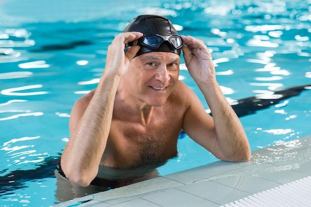 Homem idoso sorridente em uma piscina usando touca e óculos de proteção na cabeça