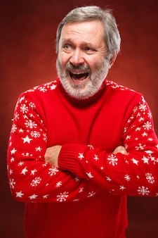 Homem idoso sorridente no vermelho