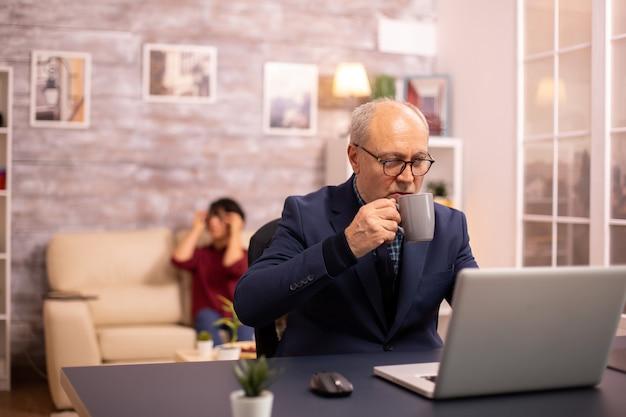 Homem idoso tomando café enquanto trabalha em um latop em uma sala de estar aconchegante e moderna