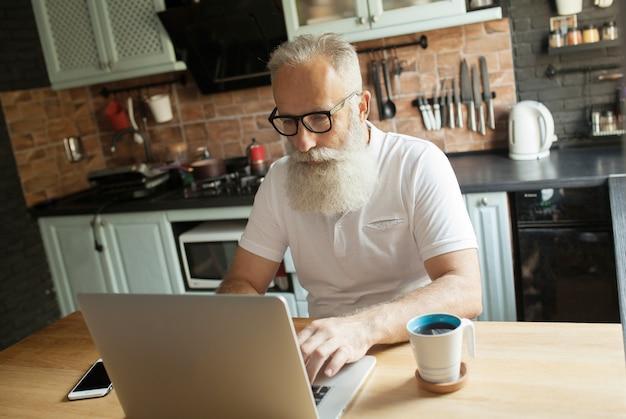 Homem idoso trabalhando no laptop, sorrindo, olhando para a tela, bebendo chá.