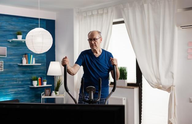 Homem idoso treino cardio em bicicleta bicicleta máquina na sala de estar para o bem-estar trabalhando a resistência do corpo