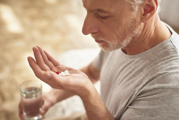 Homem idoso triste que guarda comprimidos e vidro da água.