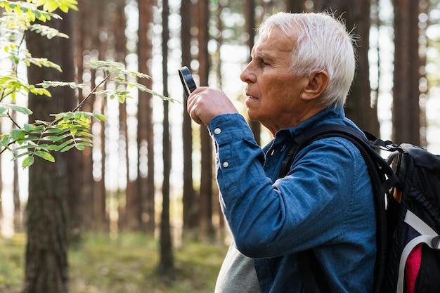 Homem idoso usando lupa enquanto explora a natureza com uma mochila