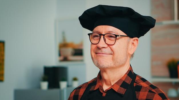 Homem idoso vestindo bonete chef sorrindo na cozinha de casa. feche o retrato do padeiro velho aposentado feliz com óculos e avental, olhando para a câmera, pronto para cozinhar massa caseira com farinha e ovos.