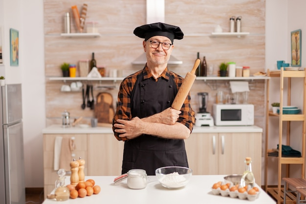 Homem idoso vestindo chef bonete sorrindo na cozinha de casa. padeiro aposentado em uniforme de cozinha preparando ingredientes de pastelaria na mesa de madeira, pronto para cozinhar massas, bolos e pães saborosos caseiros