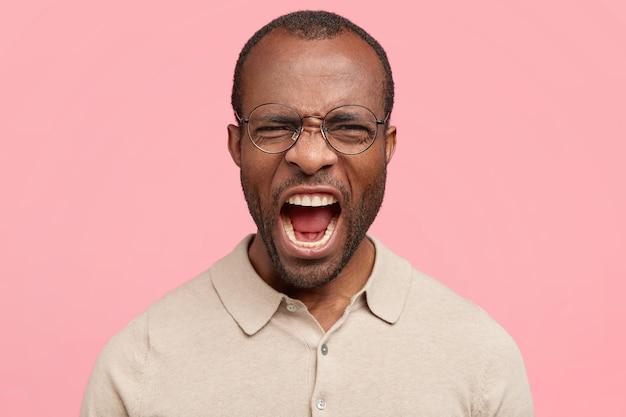 Homem imaptiente cheio de raiva, parece mal-humorado, franze a testa, grita com emoções negativas