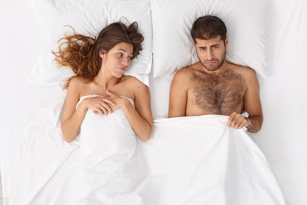 Homem impotente tem disfunção erétil, olha sob o cobertor com expressão frustrada, mulher insatisfeita está perto, tem problema de relacionamento por causa de falha sexual. conceito de saúde e impotência masculina