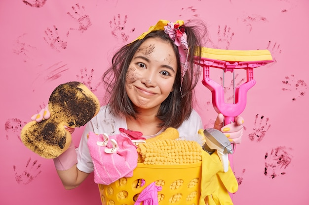 Homem inclina a cabeça e tem cara suja segura uma esponja suja e o esfregão deixa a casa em ordem antes das férias isolado em rosa