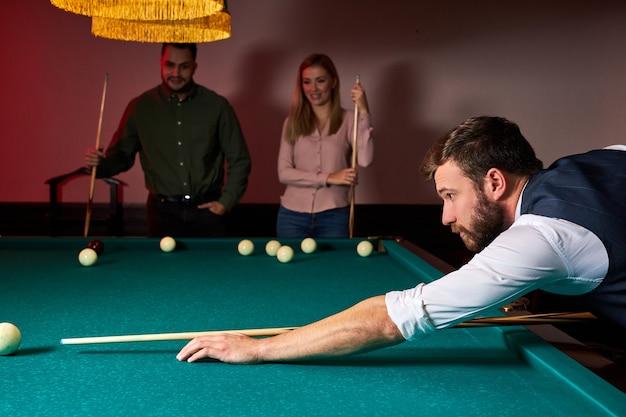 Homem inclinado sobre a mesa enquanto joga sinuca, ele está concentrado no jogo, tendo momentos de lazer
